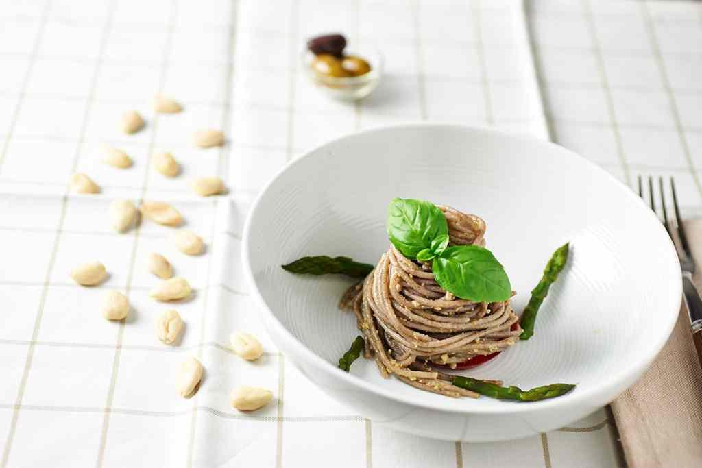 Spaghetti di grano saraceno con pesto di mandorle e olive, asparagi e basilico